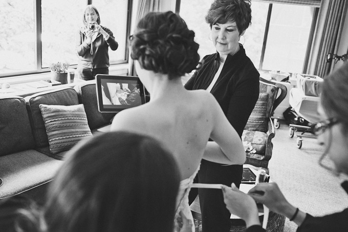 Bride uses an iPad to film her dress being tied